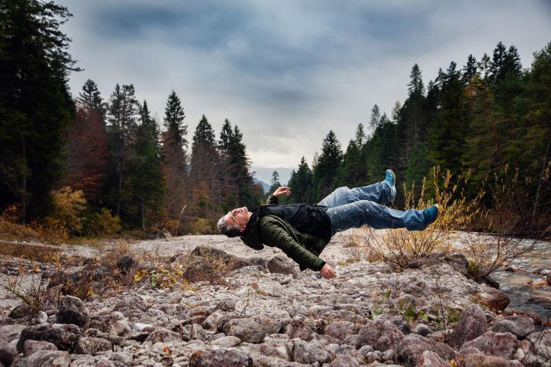 Man Levitating Over Rocks Land Against Sky