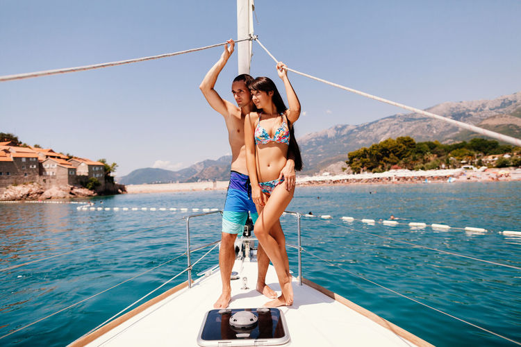 Mid Adult Couple Standing On Yacht Sailing In Sea