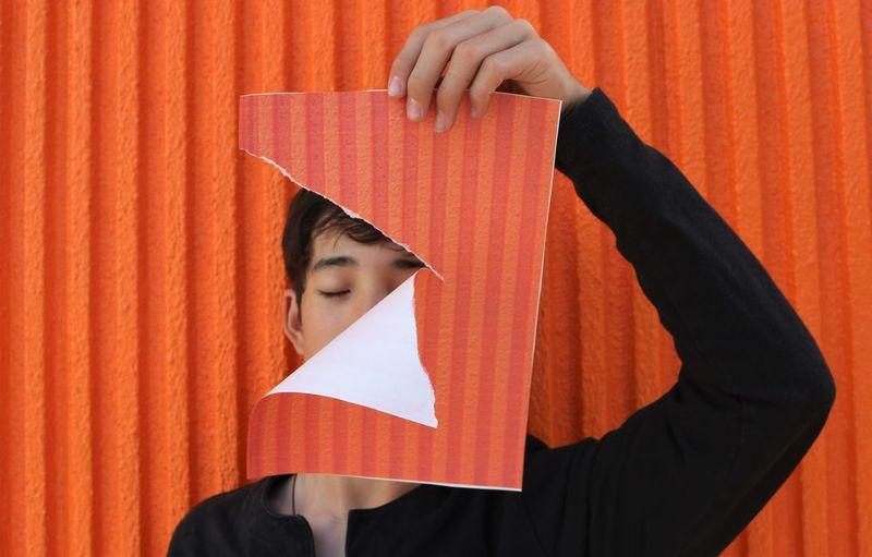 Portrait of boy standing against orange curtain