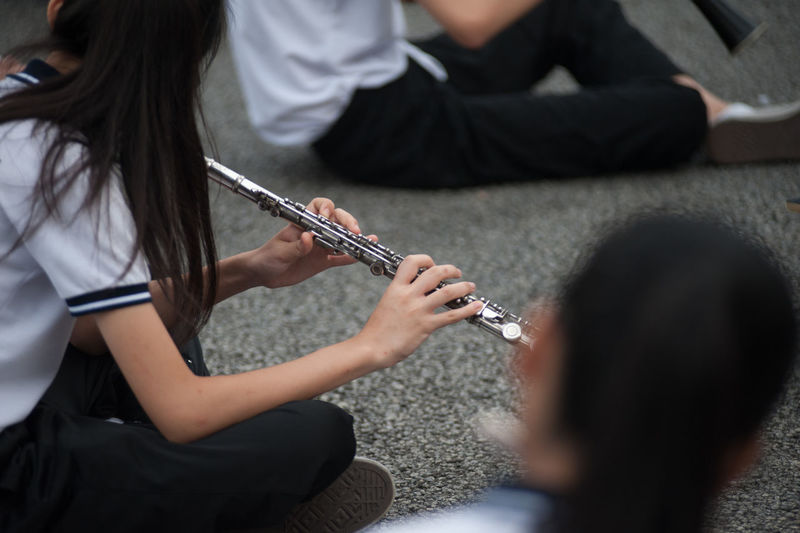 School girls playing flutes while sitting on footpath