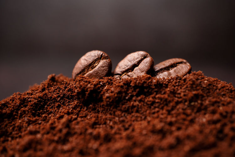 Closeup of three coffee beans at the mixed heap of roasted coffee with copy space