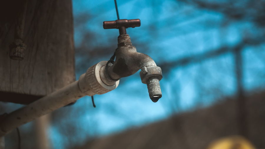Tap Drops Flowing Water Focus On Foreground No People Metal Day Representation Human Representation Close-up Faucet Art And Craft Wall - Building Feature Low Angle View Outdoors Wood - Material Cross Creativity Nature Male Likeness Rusty Sculpture Craft