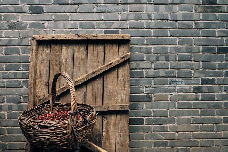 Berries in wicker basket against brick wall