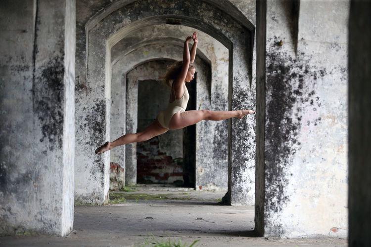 Full length of woman dancing in corridor of abandoned building