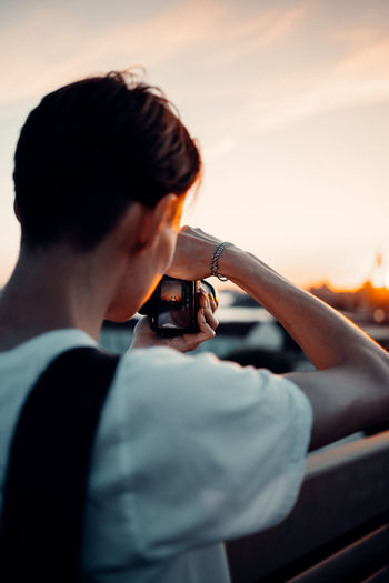 Portrait of man holding camera against sky during sunset