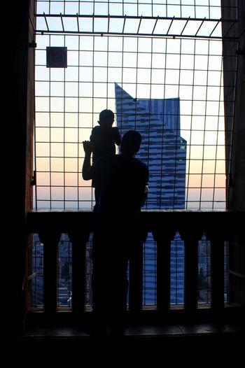 Silhouette men on window against sky