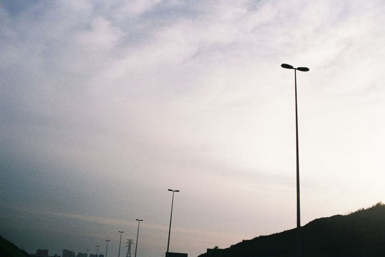 Low angle view of silhouette street light against sky