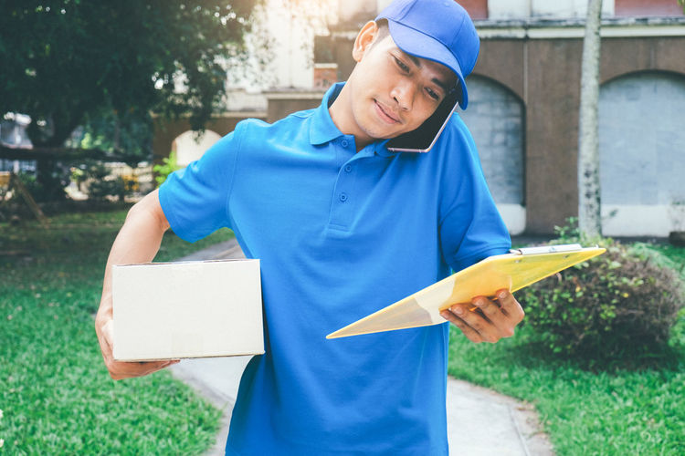 Delivery man with package talking on mobile phone