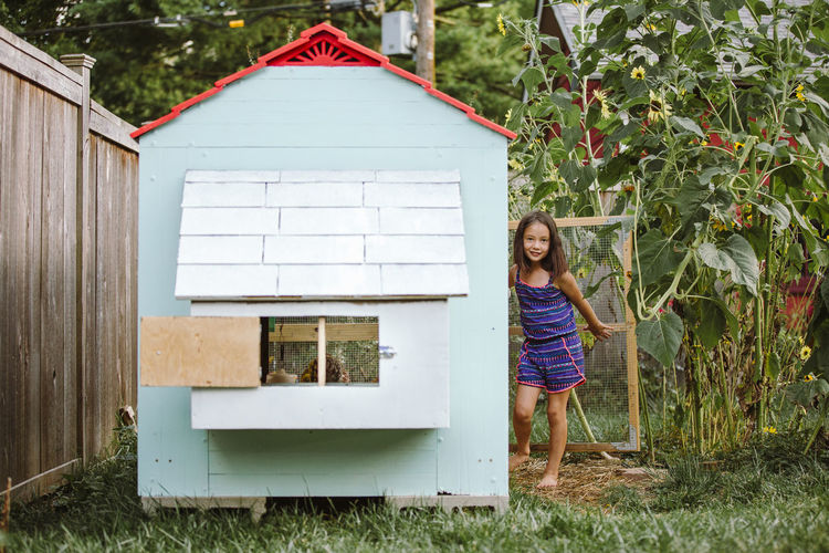 Rear view of girl standing by house