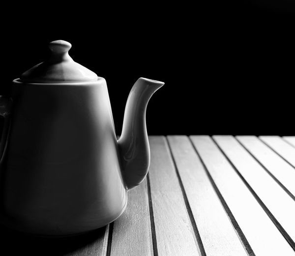 Part of vintage white ceramic teapot on wood planks table floor with sunlight on black background in black and white with low key style Low Key Shape Curve Wooden Plank Table Light Shadow Shade Black And White Dark Tone Black Background Coffee Pot Lines Pattern Detail Surface Copy Space Vintage Style EyeEm Selects Teapot Lid Tea - Hot Drink Black Background Close-up Ceramics Porcelain  Pot