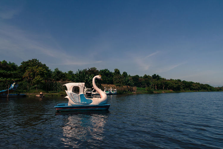 Swan Shaped Pedal Boat Moored At Lake Against Blue Sky