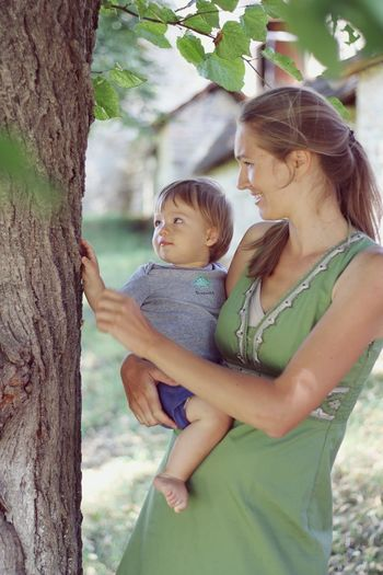 Mother and daughter on tree trunk