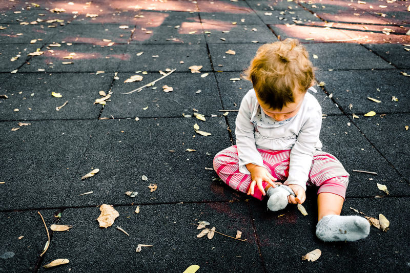 High angle view of girl playing with dry leaves