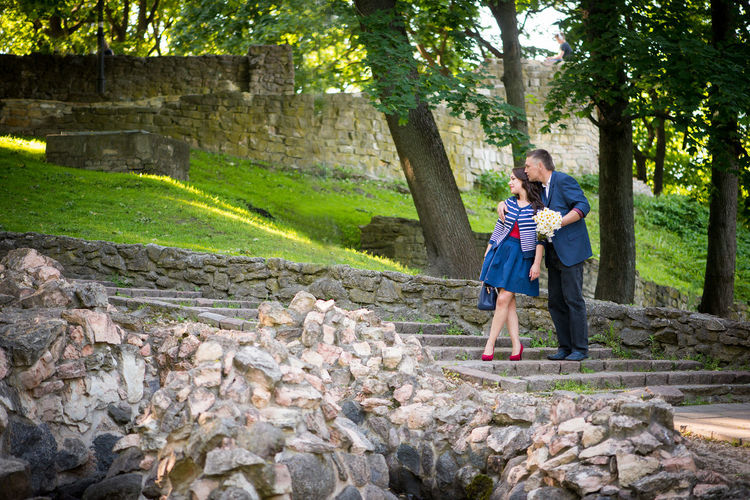 Couple looking away while standing on steps at public park
