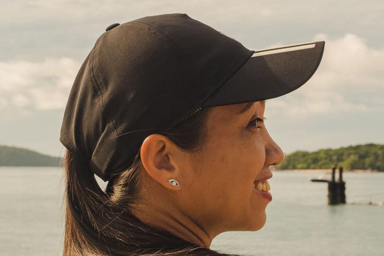 Portrait of woman wearing hat against lake