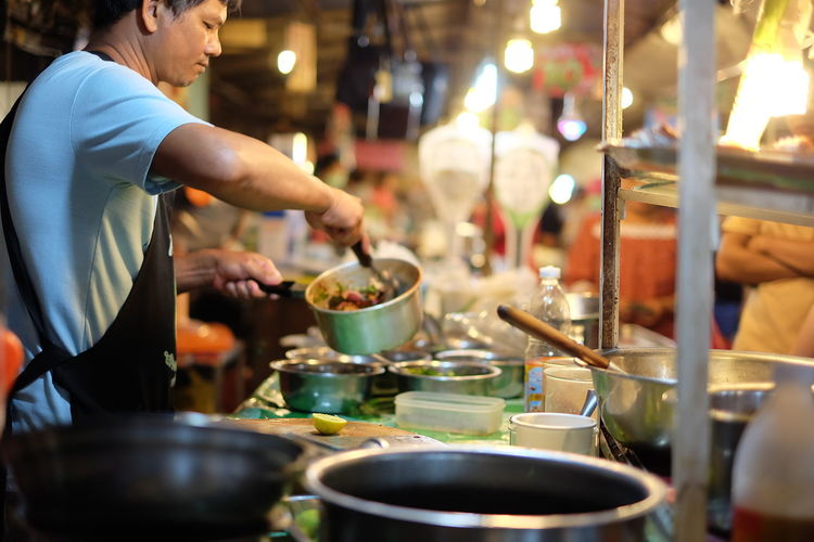 Side view of male vendor preparing food at night