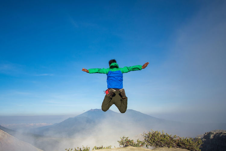 Rear view of man jumping on mountain against blue sky