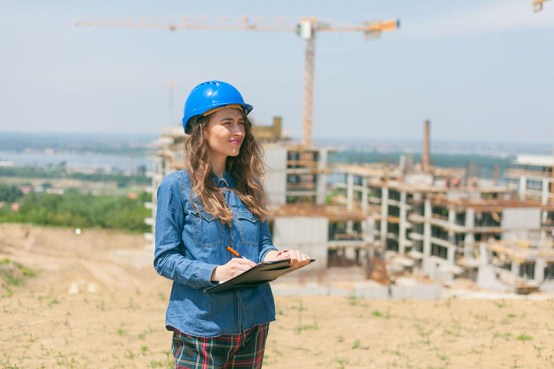 Young woman wearing hat standing at construction site