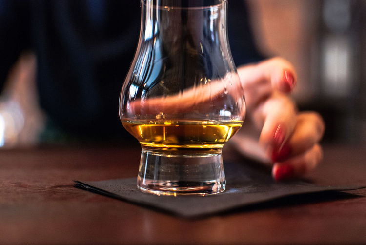 Midsection Of Woman Having Whiskey At Table In Bar