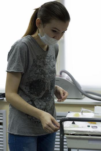 Female tattoo artist standing by rack in studio
