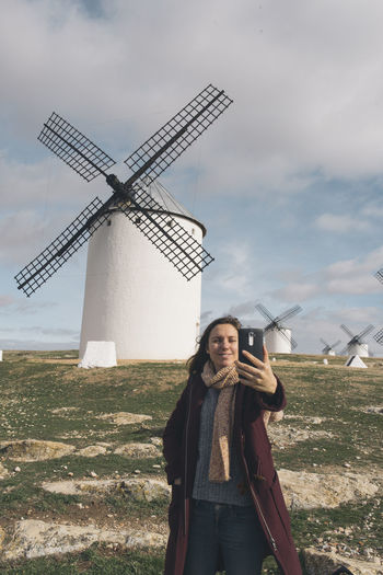 Woman taking selfie while standing against traditional windmills on landscape