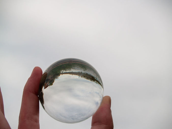 Close-up of hand holding glass against sky