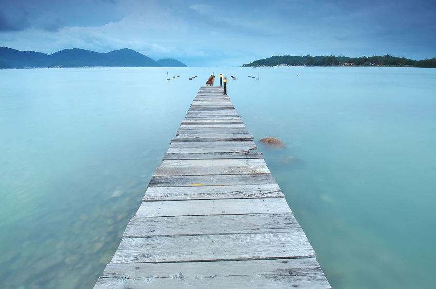 leading line of a wooden jetty during foggy day Beauty In Nature Bridge Empty Fishing Focus On Foreground Fog Geometric Haze Jetty Lake Leading Lines Loneliness Lonely Mountain Nature Pier Pontoon Reflection Scenics Tranquility Water Wooden