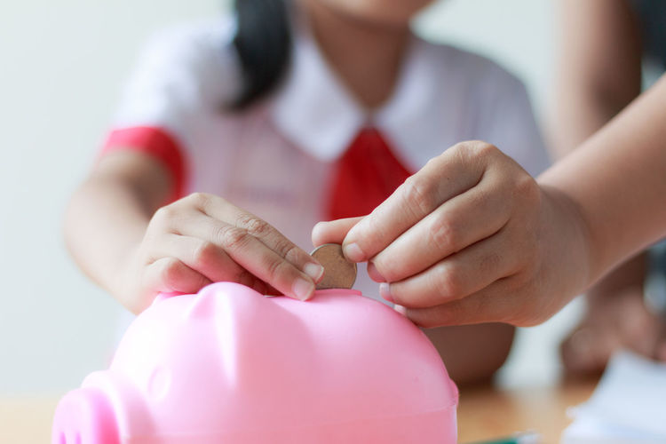 Cropped Hand Teaching Girl To Put Coin