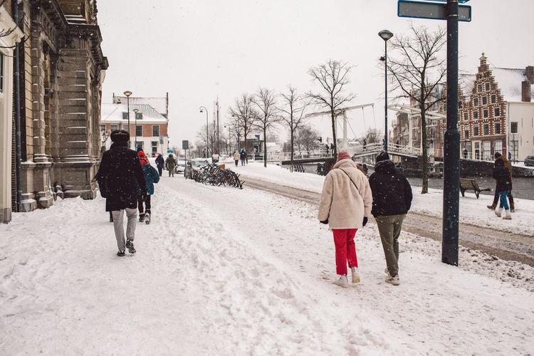 Rear view of people walking on street in winter