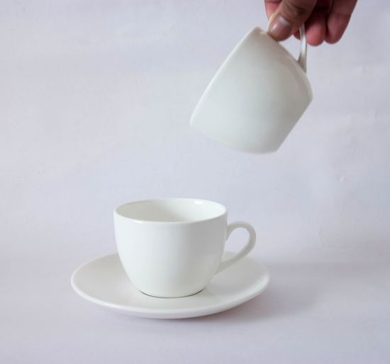 Hand of person pouring coffee in cup
