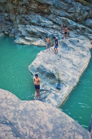High angle view of people standing amidst lagoon on rocks