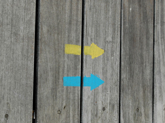 Close-Up Of Arrow Symbols On Wooden Fence