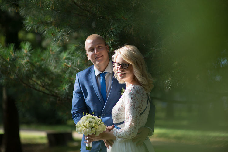 Portrait of bride and groom standing by trees at park