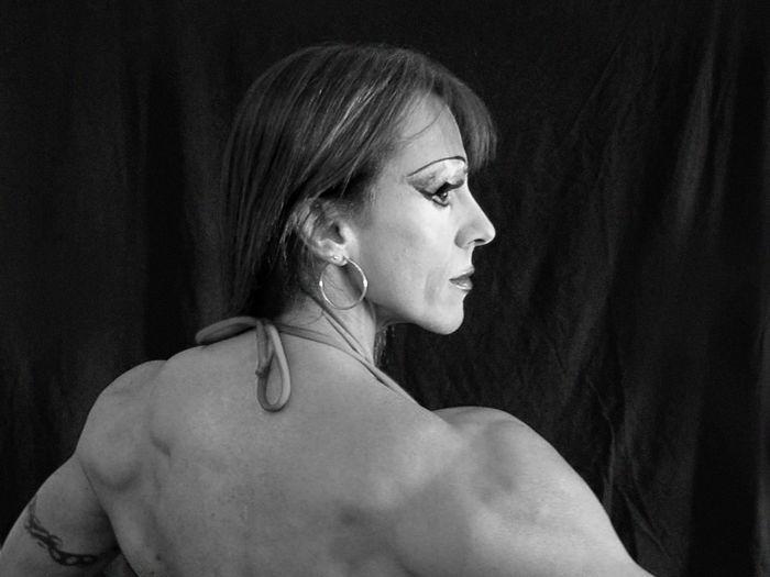 Rear view of muscular woman looking away in dark