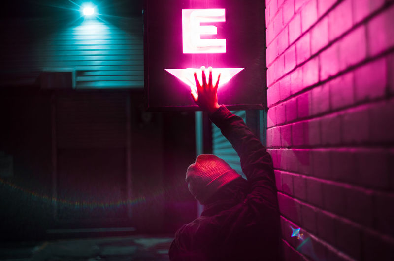 Rear View Of Woman Touching Neon Sign By Wall At Night