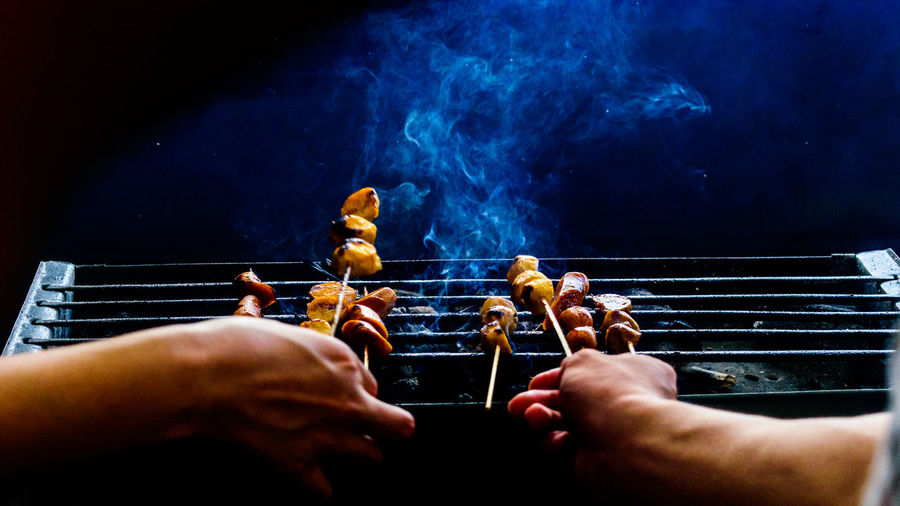 Cropped hands holding skewers with meat on barbecue grill at night