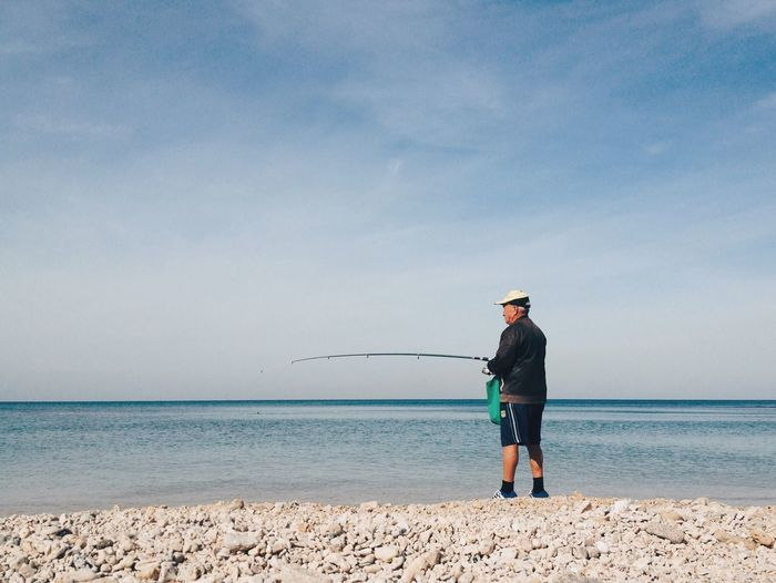 Enjoy The New Normal Sea Fishing Horizon Over Water One Person Real People Full Length Water Standing Cap Tranquil Scene Outdoors Men Day Nature Beach Fishing Tackle Sky Scenics Beauty In Nature Fishing Pole מיים