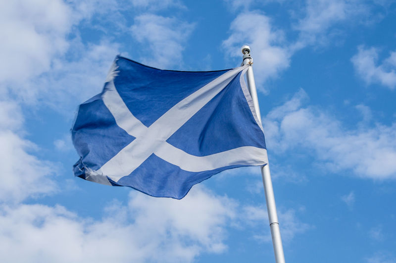 Low angle view of scottish flag against blue sky