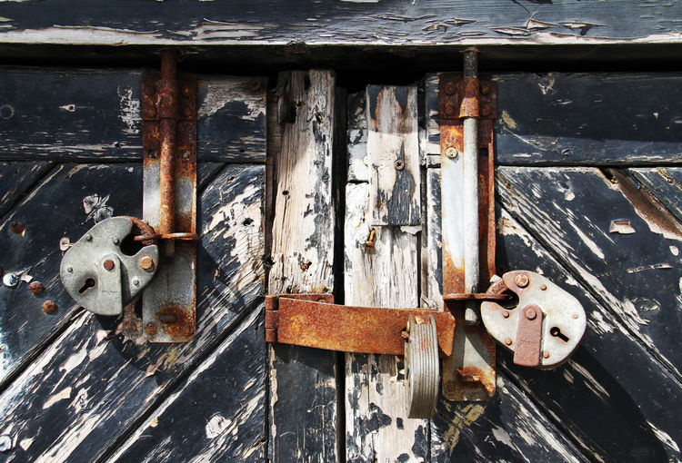 Behind lock and key Wood Closed Deterioration Latch Run-down Padlock Protection Close-up Security Lock Safety Abandoned Outdoors Weathered Entrance Door Old Wood - Material Rusty No People Metal Decline