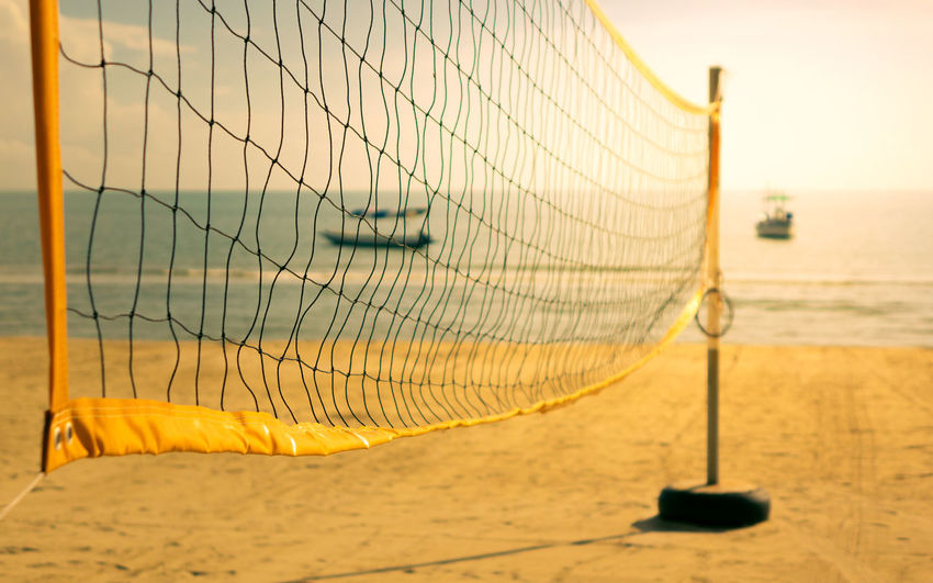 Close-up of beach volleyball net on beach against sky