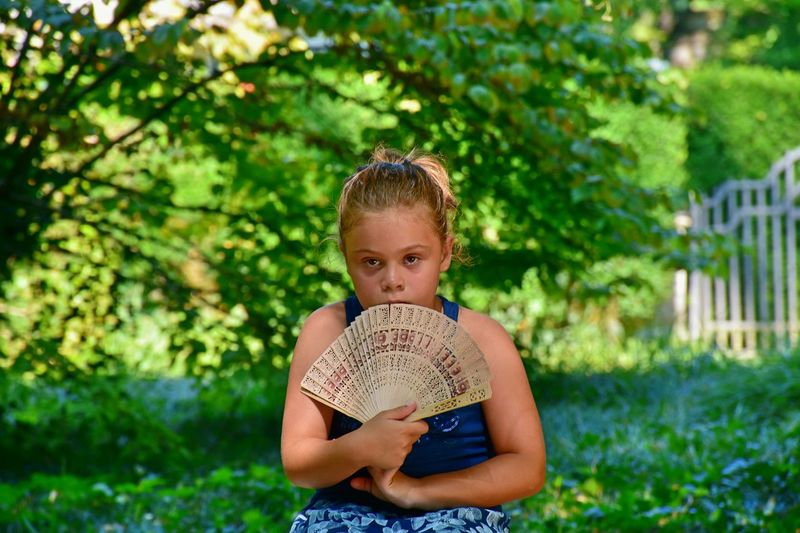 Portrait of girl holding folding fan against trees