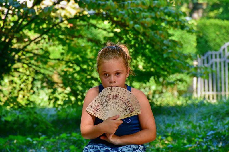 Portrait Of Girl Holding Folding Fan Against Trees
