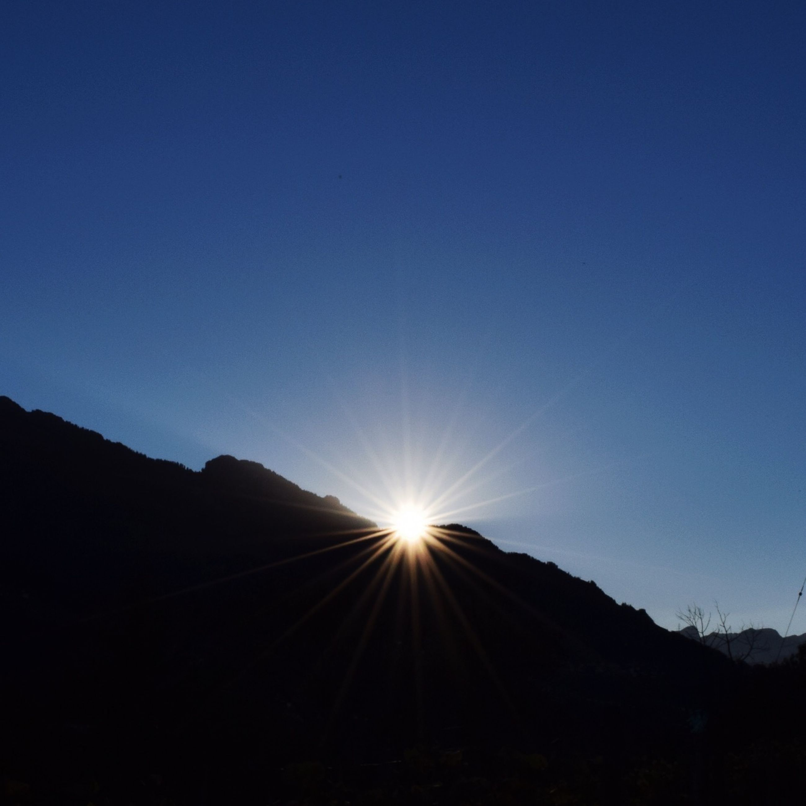 clear sky, copy space, silhouette, sun, mountain, tranquility, tranquil scene, scenics, blue, beauty in nature, sunlight, nature, mountain range, sunbeam, lens flare, low angle view, landscape, idyllic, outdoors, non-urban scene
