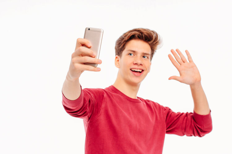Portrait of smiling young man using mobile phone against white background