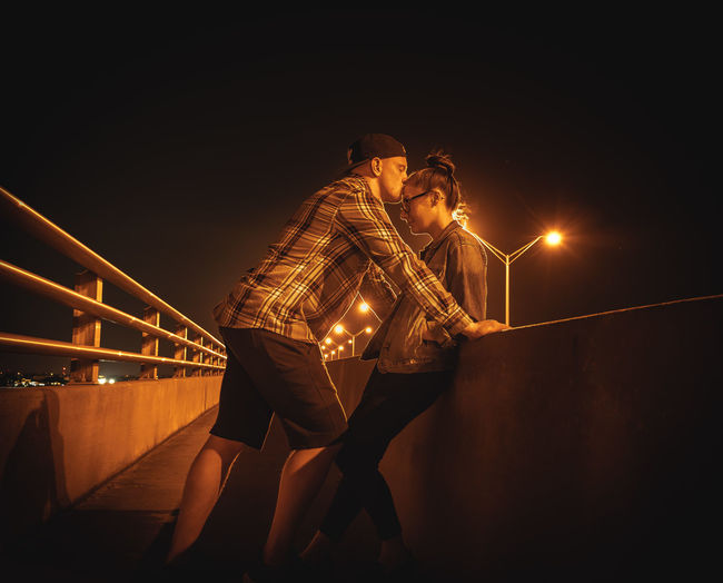 Side view of boyfriend kissing on girlfriend forehead in city at night