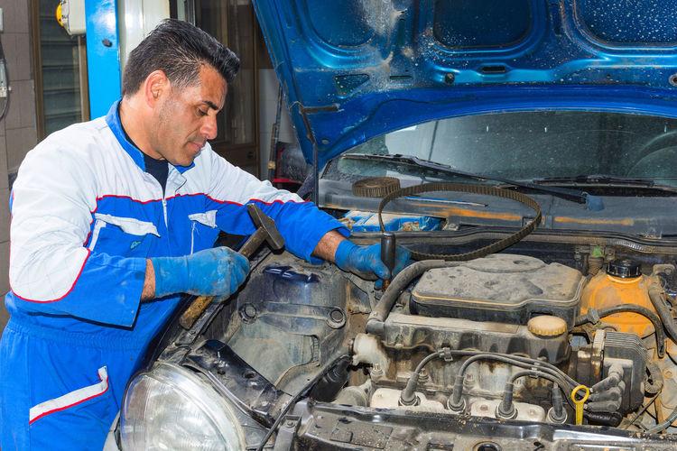 Mature mechanic repairing car