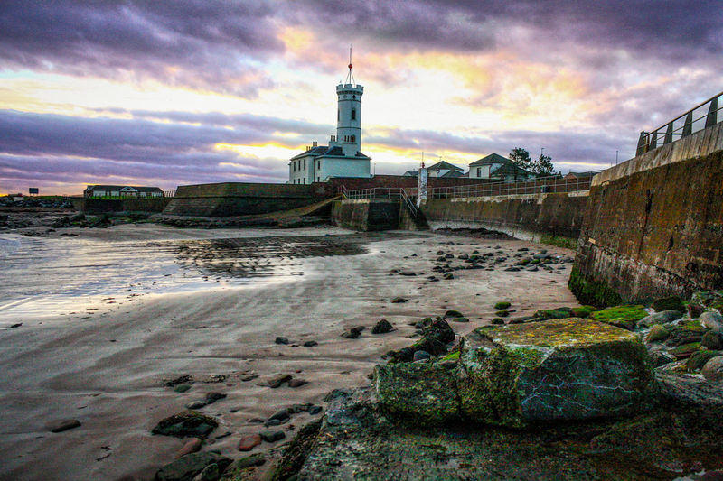 Low tide at the Signal Tower Wall Beach Sea Building No People Rocks And Water Sky Structure Sunset Tranquil Scene Outdoors