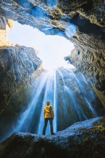 Standing underneath one of the most picturesque waterfalls in the world Check out my prints at http://simonmigaj.com/shop/ and visit my IG http://www.instagram.com/simonmigaj for more inspirational photography from around the world. Lifestyles One Person Real People Rock Leisure Activity Waterfall Standing Rear View Full Length Rock - Object Nature Beauty In Nature Scenics - Nature Hiking Mountain Flowing Water Outdoors Iceland Solid Day