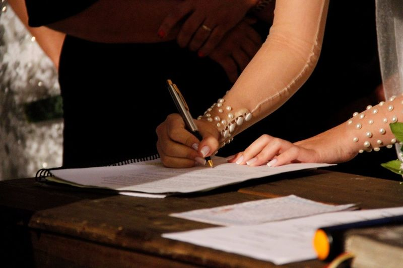 Cropped Image Of Bride Signing Document During Wedding Ceremony