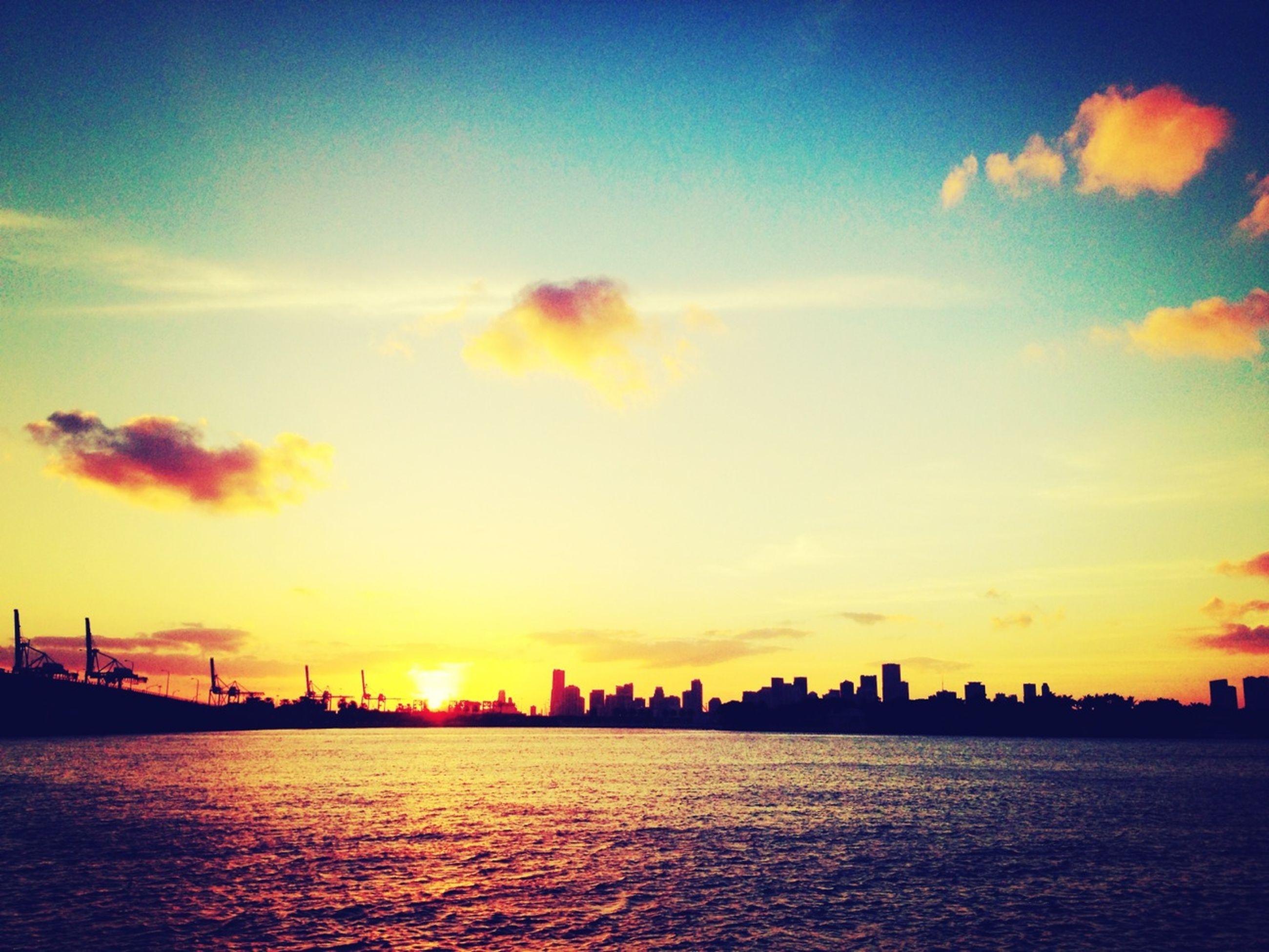 sunset, waterfront, building exterior, architecture, water, built structure, city, sky, cityscape, orange color, sea, silhouette, urban skyline, skyscraper, skyline, river, scenics, tower, cloud - sky, beauty in nature
